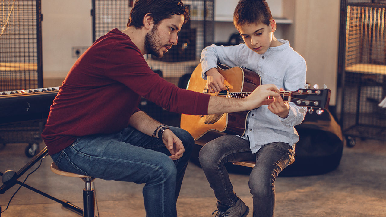 Photo of a guitar teacher giving a lesson to a young boy