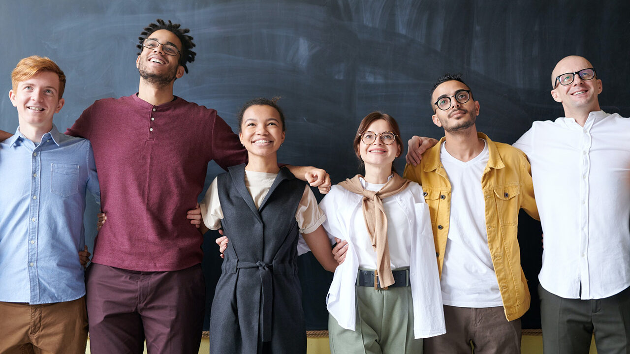 Photo of six men and women standing in front of a chalkboard