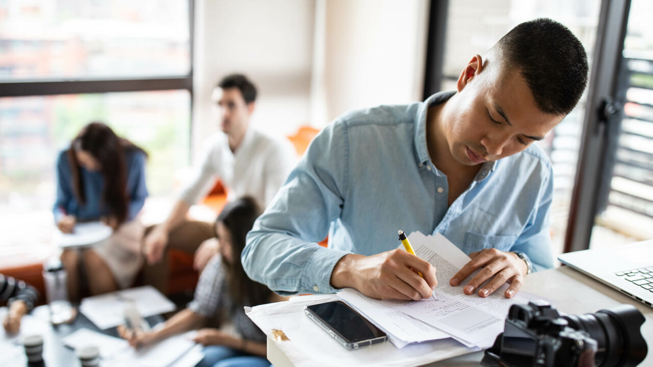 Photo of a man in an office. He is making notes on a document with a pencil and there are three other people in the background having a conversation.