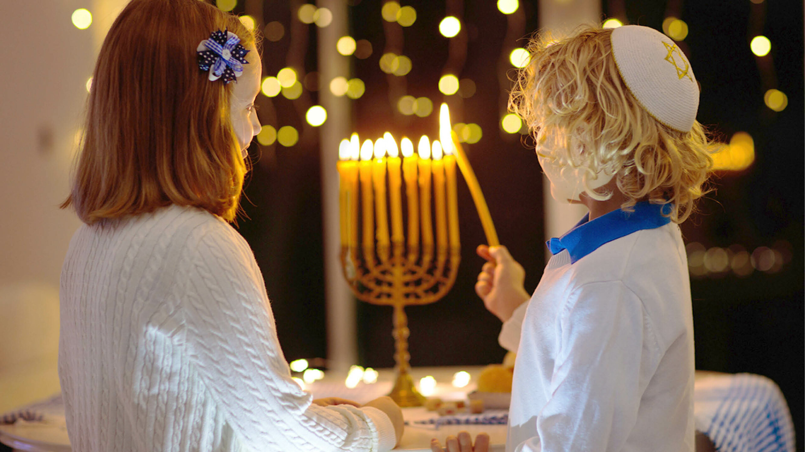 Two young children lighting a candle on a menorah