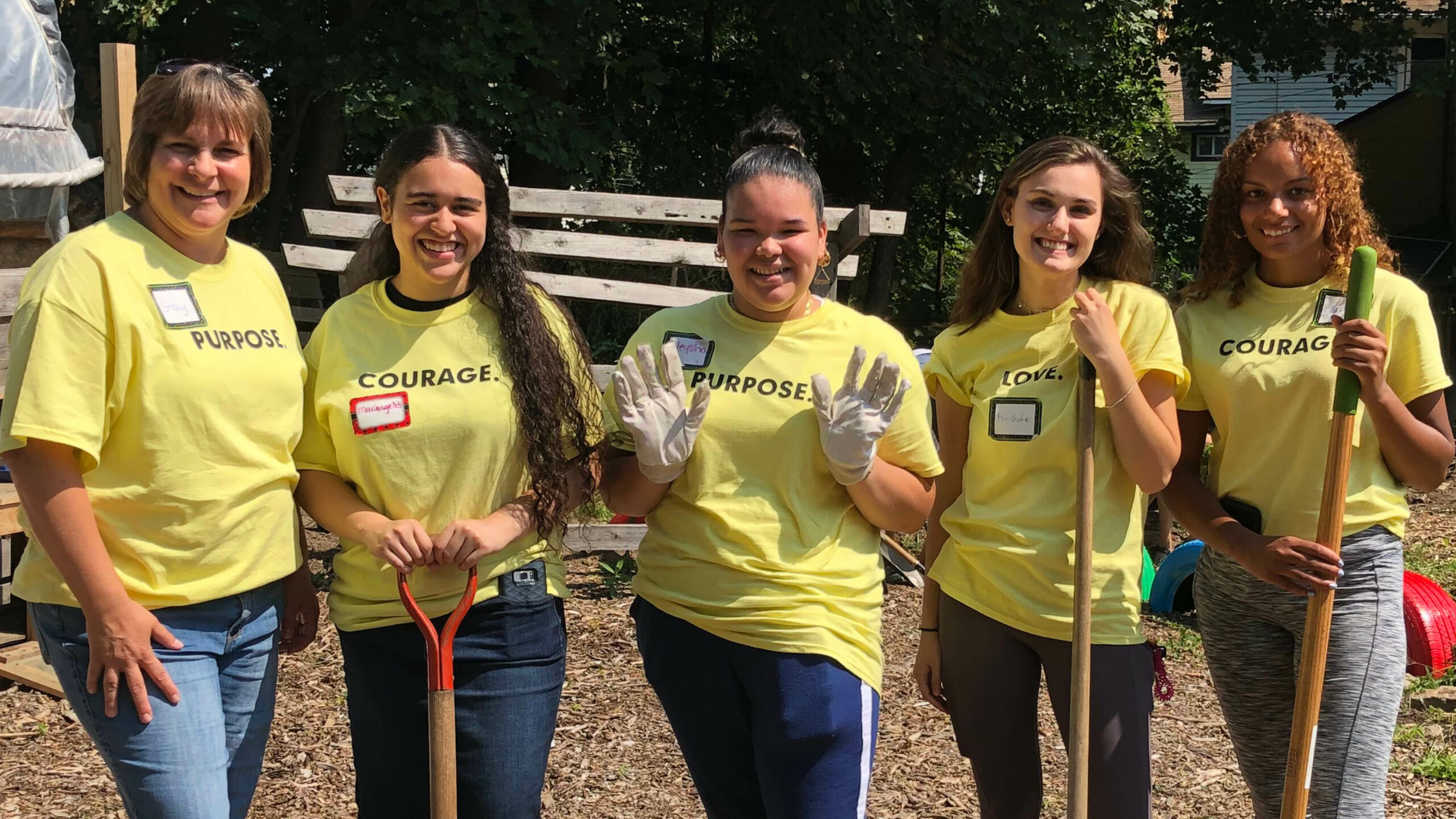 Photo of five women volunteers with shovels and rakes at a worksite.